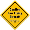 This Low Flying Aircraft metal sign measures 12 inches by 12 inches and weighs in at 1 lb(s). This metal sign is hand made in the USA using heavy gauge american steel and a process known as sublimation, where the image is baked into a powder coating for a durable and long lasting finish. This metal sign is drilled and riveted for easy hanging.